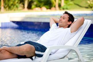 Man Relaxing by Pool in Chaise Lounge
